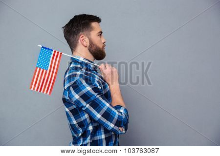 Side view portrait of a casual man holding USA flag over gray background