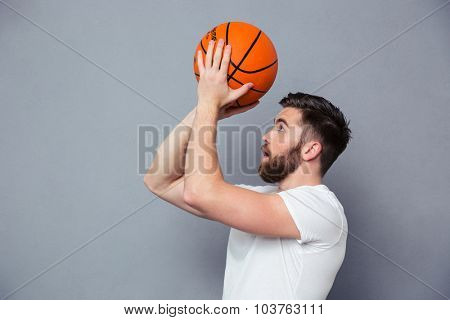 Portrait of a young man reading to throw basket ball over gray background