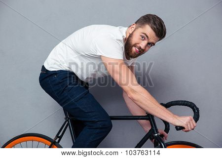 Portrait of a smiling man riding on bicycle over gray background