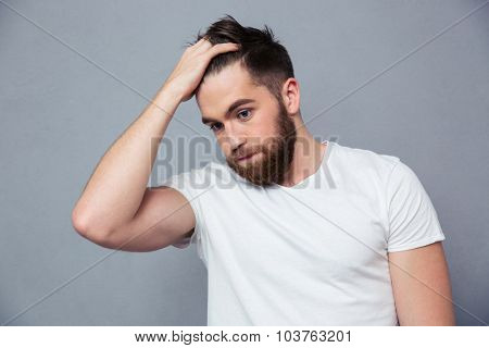 Portrait of a pensive casual man standing over gray background