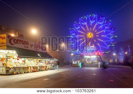 ALBA, ITALY - DECEMBER 22, 2014: Illuminated observation wheel and mobile stall with sweets on town square as part of traditional Christmas and New Year celebrations.