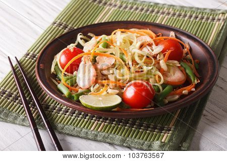 Fresh Thai Green Papaya Salad With Shrimp Close-up. Horizontal