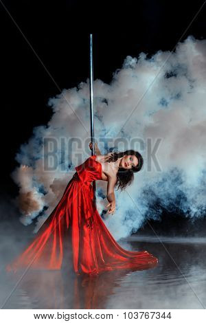 Girl Shrouded In Smoke Dancing Around A Pole Dance.