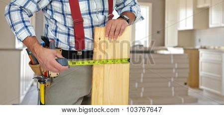 Handyman with wood plank and ruler on construction background.
