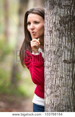 Beautiful woman playing hide and seek behind tree