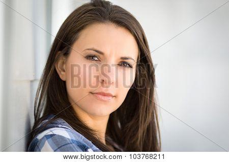 Beautiful brunette woman leaning on wall