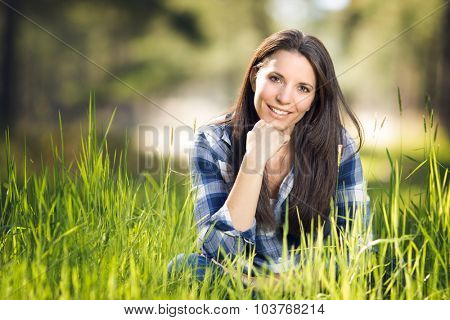 Beautiful smiling woman sitting in grass