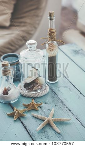 Summer interior decoration with starfishes and bottles in blue and white colors