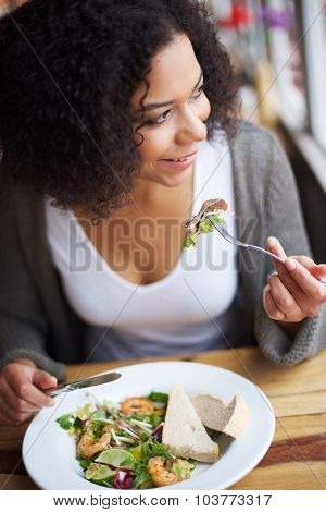 Smiling African American Woman Eating In Restaurant