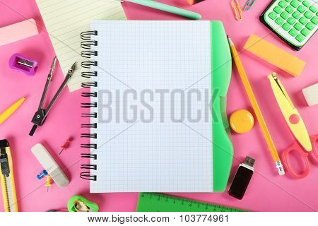 Office and student tools on pink background closeup