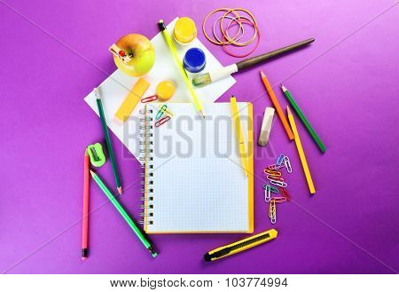 Office and student tools on purple background closeup