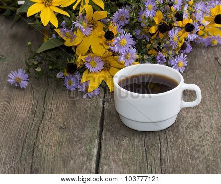 Still Life A Cup Of Coffee And Wild Flowers On An Old Table