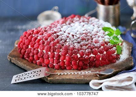 Sweet cake with raspberries on color wooden background