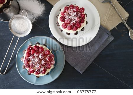 Sweet cakes with raspberries on color wooden background