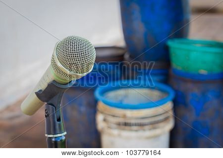 Microphone On A Stand With Background Of Blurred Plastic Garbage Container For Rubbish And Discarded