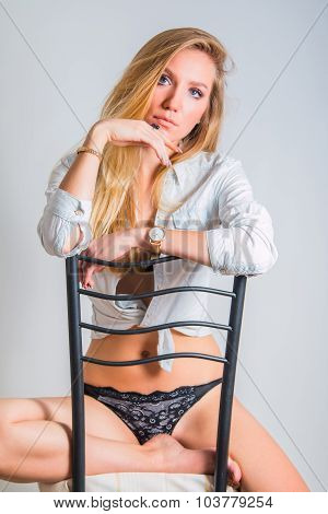 Young woman sitting on chair, fashion self confident pose, beauty concept