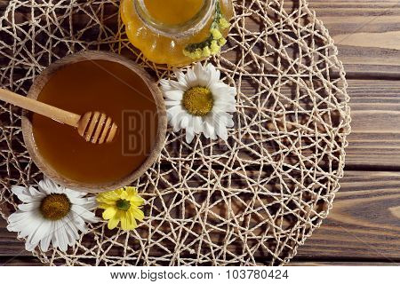 Honey in pot and in bowl, wooden dipper and flowers on wicker mat on wooden background
