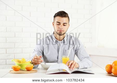 Young man having breakfast with oranges