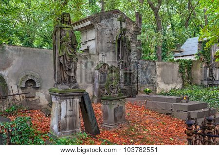 PRAGUE, CZECH REPUBLIC - SEPTEMBER 23, 2015: Statues and graves on old Olsany Cemeteries - largest graveyard in Prague with 2 million burials, created in 1680, noted for its remarkable monuments.