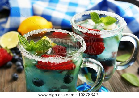 Glasses of berries juice on wooden table, closeup
