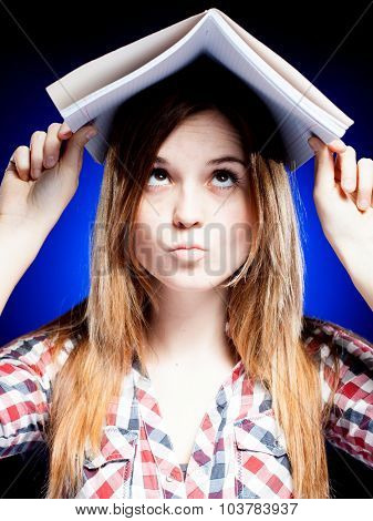 Confused And Puzzled Young Girl Holding Exercise Book On Her Head