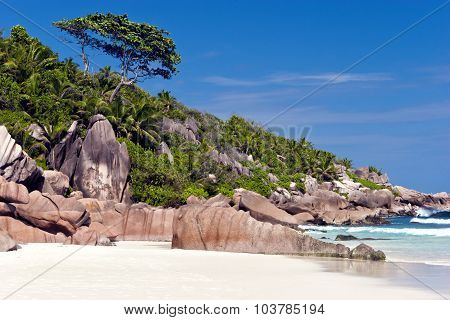 Sandy beach on tropical Indian Ocean island of Seychelles with big granite boulders lush green trees