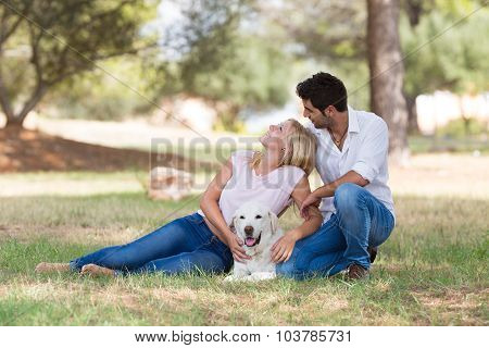 beautiful young couple with old senior labrador dog in the nature