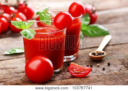 Glasses of tomato juice on wooden table, closeup