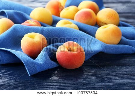 Ripe apricots with napkin on wooden table close up