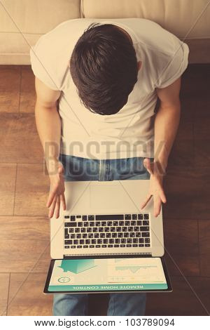 Young man sitting on floor with laptop in room