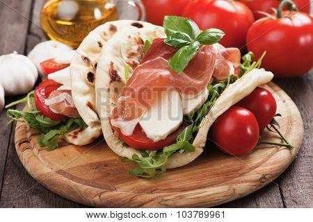 Piadina Romagnola, Italian Flatbread Sandwich with Prosciutto, mozzarella cheese, tomato and rocket salad