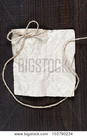 Blank Crumpled Sheet Of Paper With Rope Bow On The Dark Wooden Table
