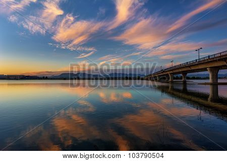 Playful clouds, pastel-coloured sky and water, concrete bridge, and mountains