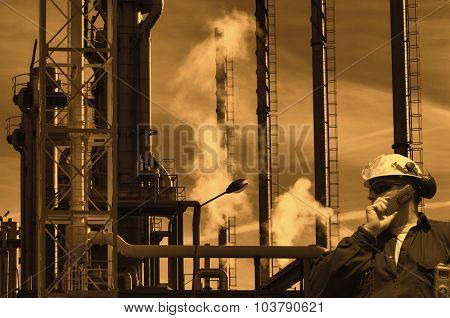 sunset over oil and gas refinery, worker in foreground