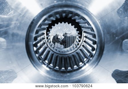 two industry workers seen through a giant cogwheels axle, steel industrial