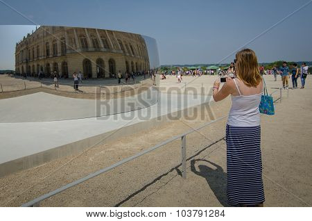 Tourist takes photo at Palace of Versailles
