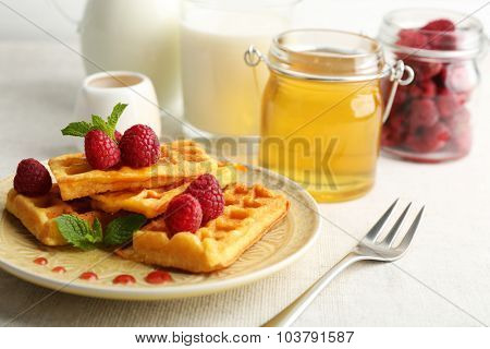 Sweet homemade waffles with fresh raspberries on plate, on light background