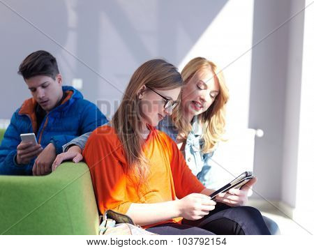 students group working on school  project  together on tablet computer  at modern university