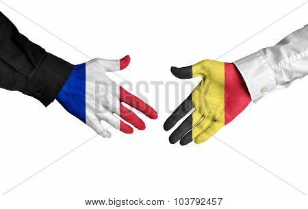 France and Belgium leaders shaking hands on a deal agreement