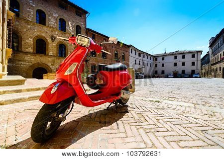 Red italian Piaggio Vespa scooter in the historical center of the Tuscan town