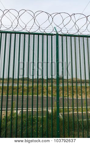 Green Fence With Razor Wire Guarding French Ferry Terminal.