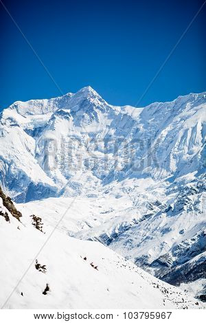 Mountain inspirational landscape in Himalayas Annapurna 2 Nepal. Mountain ridge with ice and snow ov