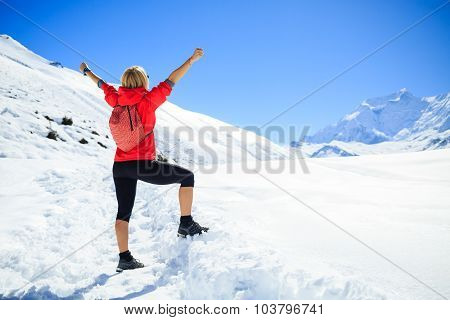 Young happy woman hiker with arms hands outstretched in winter mountains. Climbing inspiration and m