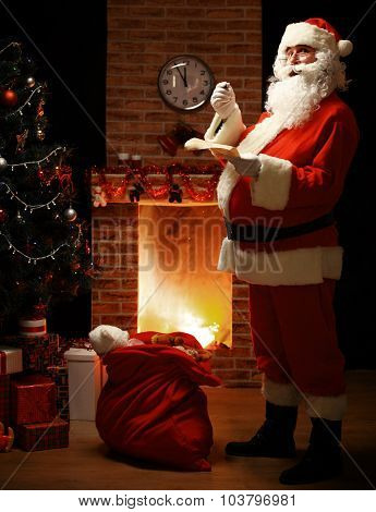 Portrait Of Happy Santa Claus Standing At His Room At Home Near Christmas Tree And Big Sack And Read