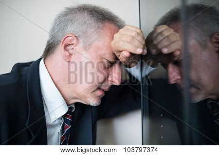 Portrait of a tired and stressed businessman lying against a glass