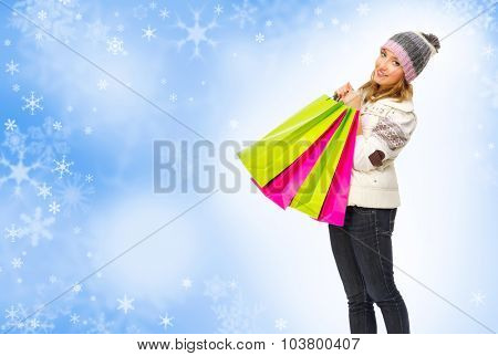 Young smiling girl with bags on winter background