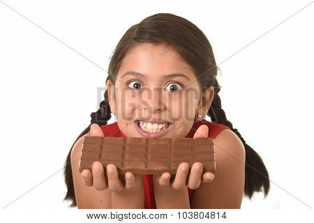 Latin Child In Red Dress Holding With Both Hands Big Chocolate Bar In Front Of Her Crazy Excited Fac