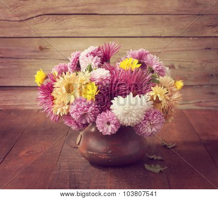 Still life with colourful chrysanthemums bunch on old wooden table. Toned image