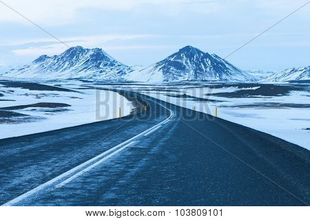 The road at  twilight through the snow capped mountains  in winter. Northeast of Iceland .  The Ring Road  (Route 1) of Iceland, between Egilsstadir and  Akureyri