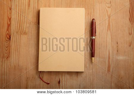 blank book closed with pen by the side